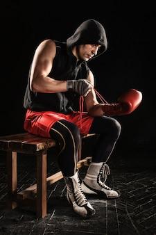 Der junge männliche athlet kickboxen sitzt und schnürt handschuh auf einem schwarzen