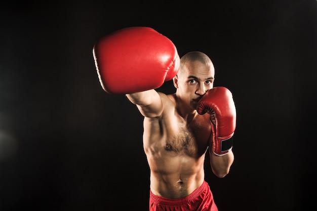 Der junge männliche athlet tritt auf einem schwarzen kickboxen