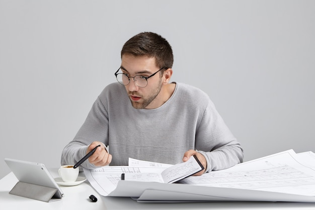 Der junge männliche designer starrt auf den bildschirm des tablets und hat die frist, um die zeichnungsskizzen fertigzustellen.