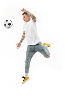 Der junge mann als fußballspieler, der den ball im studio auf einem weißen hintergrund springt und tritt.