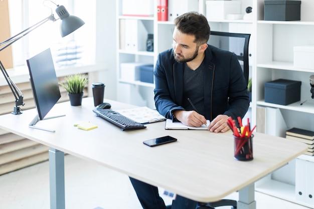 Der junge mann arbeitet im büro an einem computertisch mit dokumenten, diagrammen und telefon.