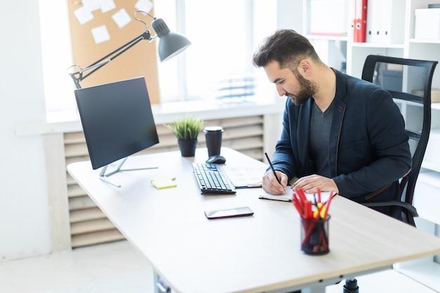 Der junge mann arbeitet im büro an einem computertisch mit dokumenten