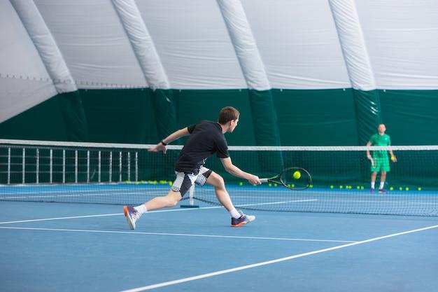 Der junge mann auf einem geschlossenen tennisplatz mit ball