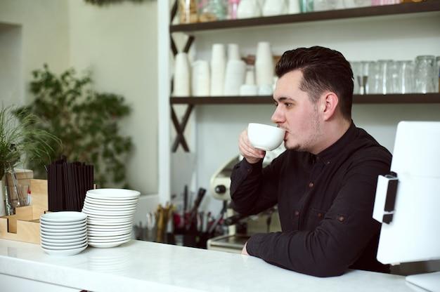 Der junge mann barista im schwarzen hemd trinkt kaffee an der bar