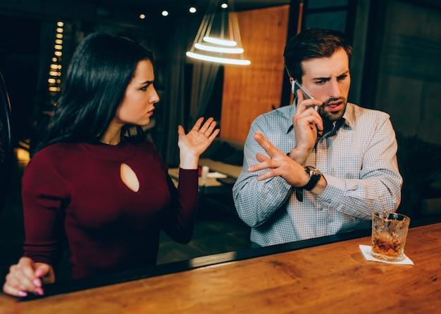 Der junge mann beantwortet gerade einen anruf, während er ein date mit einem schönen mädchen hat. sie ist verärgert und sie mag es nicht. sie versucht dem mann davon zu erzählen, aber er weigert sich, ihr zuzuhören.