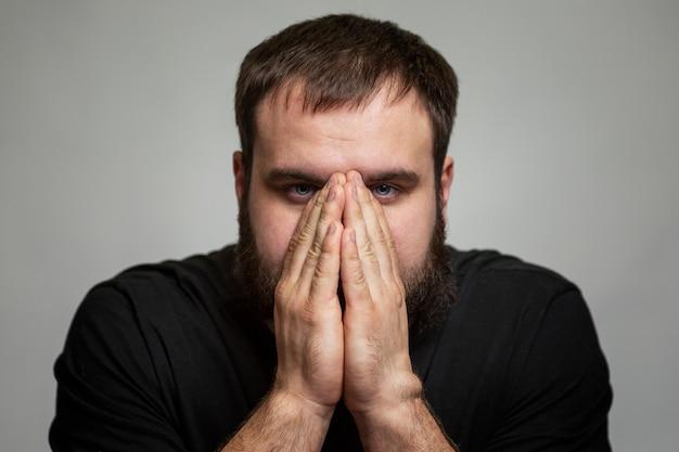Der junge mann bedeckte sein gesicht mit den händen. brünette in einem schwarzen t-shirt. störende emotionen. grauer hintergrund.
