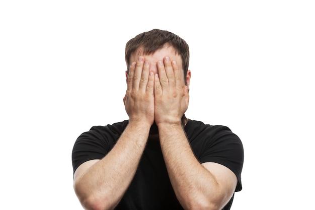 Der junge mann bedeckte sein gesicht mit den händen. brünette in einem schwarzen t-shirt. störende emotionen. isoliert auf weißem hintergrund.
