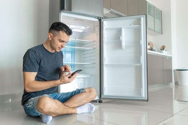 Der junge mann bestellt essen mit einem smartphone