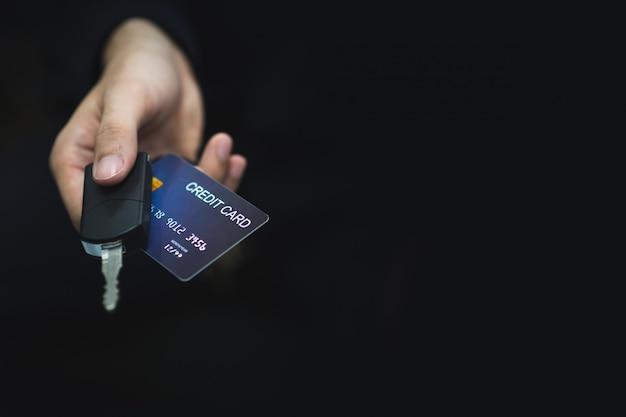 Der junge mann bezahlte die autoschuld mit einer kreditkarte mit einem autoschlüssel in der hand.