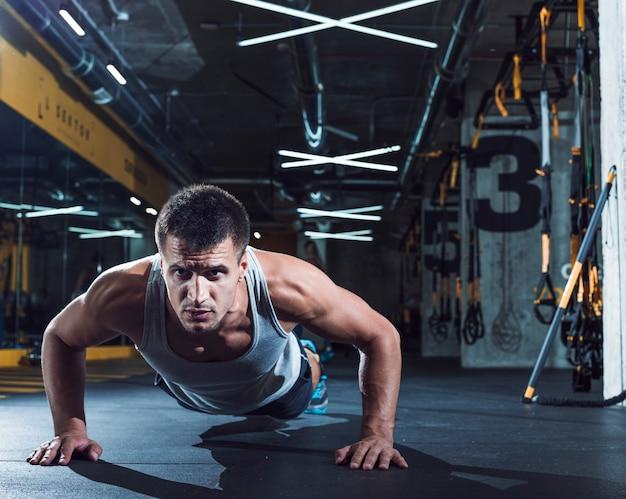 Der junge mann, den das handeln drückt, ups in fitness-club