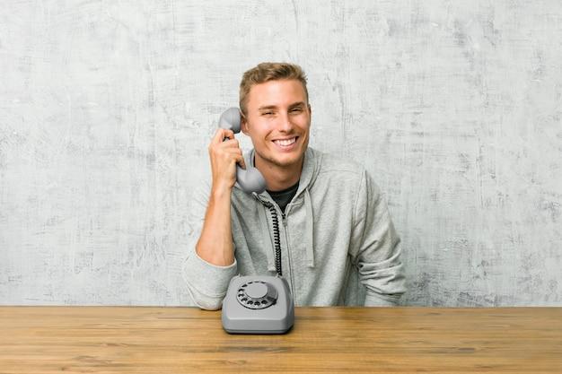 Der junge mann, der an einem weinlesetelefon spricht, lacht und schließt augen, fühlt sich entspannt und glücklich.