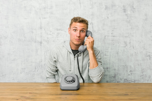 Der junge mann, der an einem weinlesetelefon spricht, zuckt die schultern und die offenen augen, die verwirrt werden.