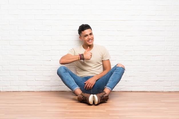 Der junge mann, der auf dem boden gibt daumen sitzt, up geste