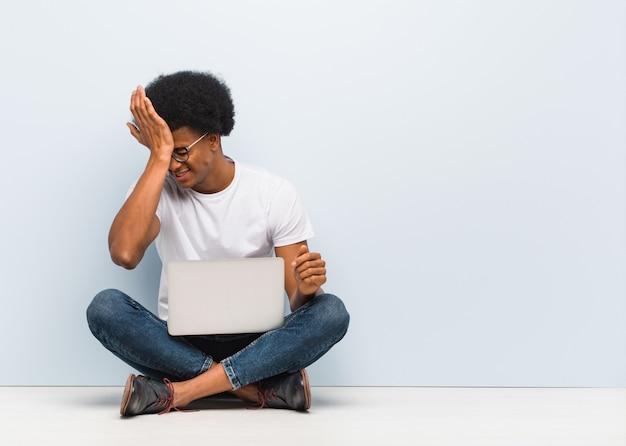 Der junge mann, der auf dem boden mit einem laptop vergesslich sitzt, verwirklichen etwas