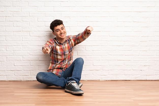 Der junge mann, der auf dem boden sitzt, zeigt finger auf sie beim lächeln