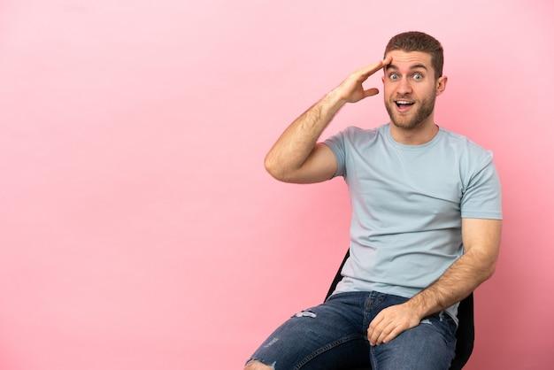 Der junge mann, der auf einem stuhl über isoliertem rosa hintergrund sitzt, hat etwas erkannt und beabsichtigt die lösung