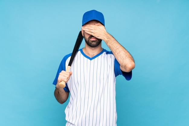 Der junge mann, der baseball über lokalisierter blauer bedeckung spielt, mustert durch hände, möchten nicht etwas sehen