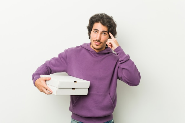 Der junge mann, der das pizzapaket zeigt seinen tempel mit dem finger, denkend hält, konzentrierte sich auf eine aufgabe