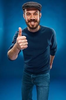 Der junge mann, der daumen zeigt, up handzeichen