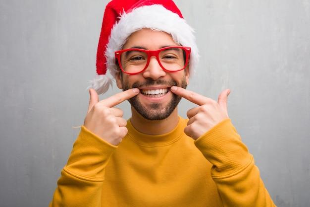 Der junge mann, der den weihnachtstag hält geschenke feiert, lächelt und zeigt mund