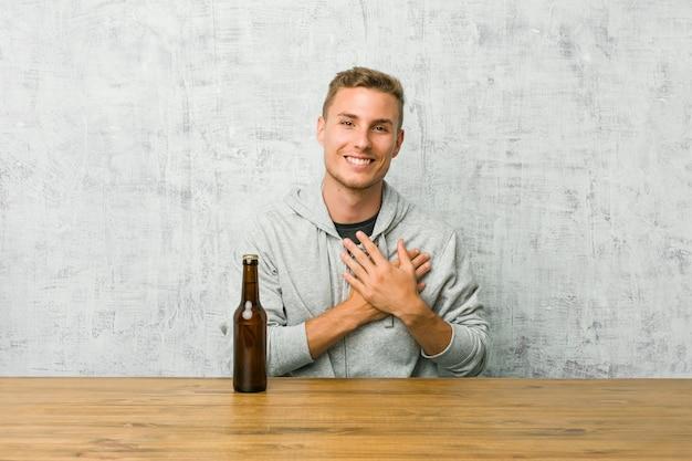 Der junge mann, der ein bier auf einem tisch trinkt, hat den freundlichen ausdruck und drückt palme zur brust. liebes-konzept.