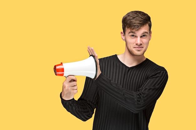 Der junge mann, der ein megaphon auf gelbem hintergrund hält