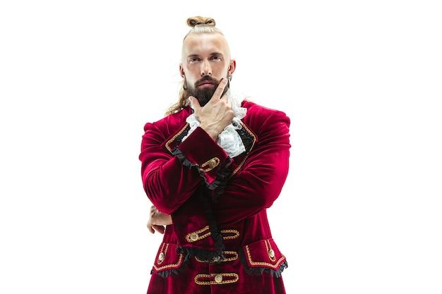 Der junge mann, der ein traditionelles mittelalterliches kostüm des marquis trägt, der im studio aufwirft. fantasie, antike, renaissance-konzept