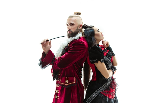 Der junge mann, der ein traditionelles mittelalterliches kostüm des marquis trägt, der im studio mit frau als marquise aufwirft