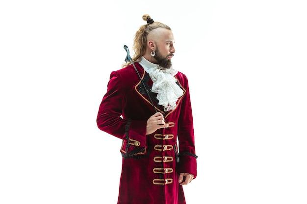 Der junge mann, der ein traditionelles mittelalterliches kostüm des marquis trägt, der im studio mit peitsche aufwirft. fantasie, antike, renaissance-konzept
