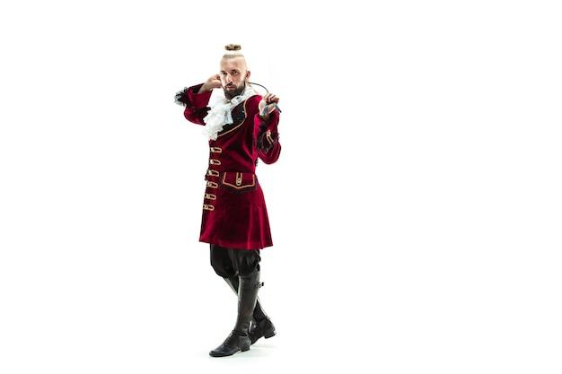 Der junge mann, der ein traditionelles mittelalterliches kostüm des marquis trägt, der im studio mit peitsche aufwirft.