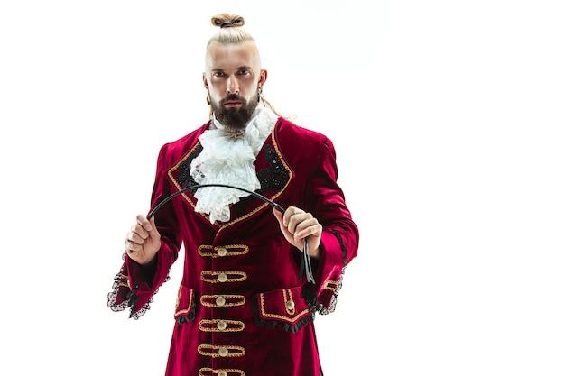 Der junge mann, der ein traditionelles mittelalterliches kostüm des marquis trägt, der im studio mit peitsche aufwirft
