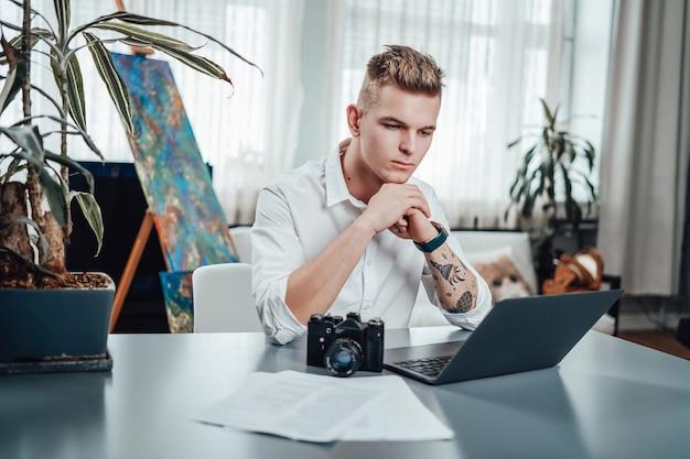 Der junge mann, der ein weißes hemd mit fotokamera trägt, erledigt seine arbeit am tisch im büro. beruflicher beruf fotograf starter.