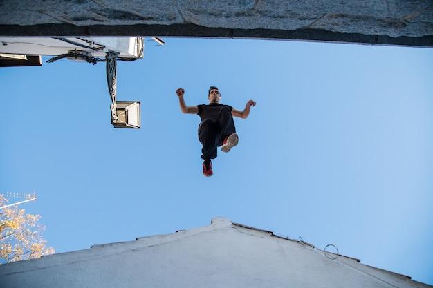 Der junge mann, der eindrucksvollen parkour tut, springen von einem dach zum anderen