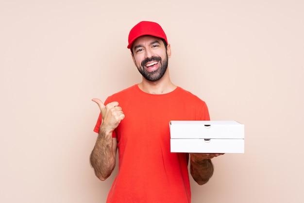 Der junge mann, der eine pizza mit den daumen hält, up geste und das lächeln