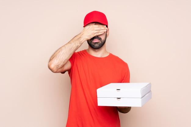 Der junge mann, der eine pizza über lokalisierter wandverkleidung hält, mustert durch hände. ich will nichts sehen