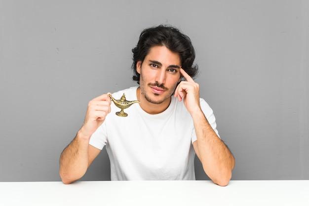 Der junge mann, der eine wunderlampe zeigt seinen tempel mit dem finger anhält und denkt, konzentrierte sich auf eine aufgabe
