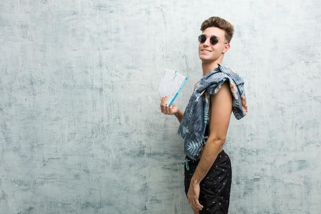 Der junge mann, der einen badeanzug hält flugtickets trägt, schaut beiseite lächelnd, nett und angenehm