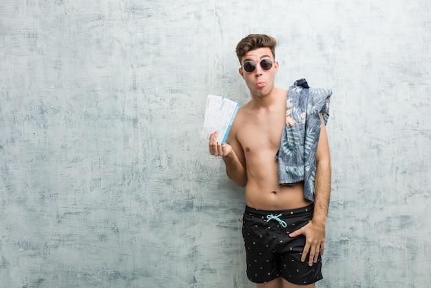 Der junge mann, der einen badeanzug hält flugtickets trägt, zuckt mit den schultern und die offenen augen, die verwirrt werden.