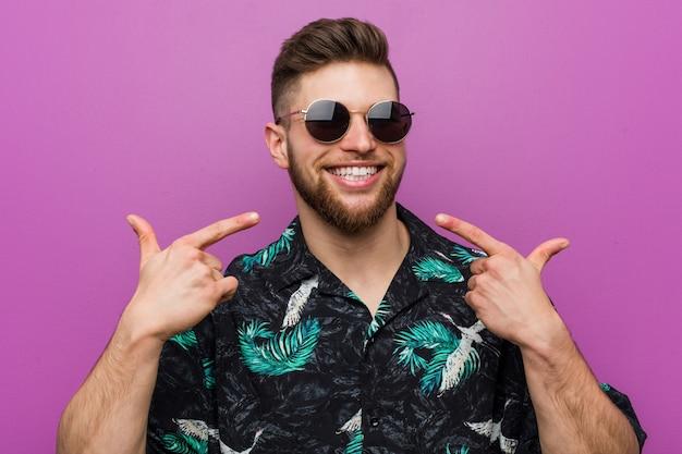Der junge mann, der einen ferienblick trägt, lächelt und zeigt finger auf mund.
