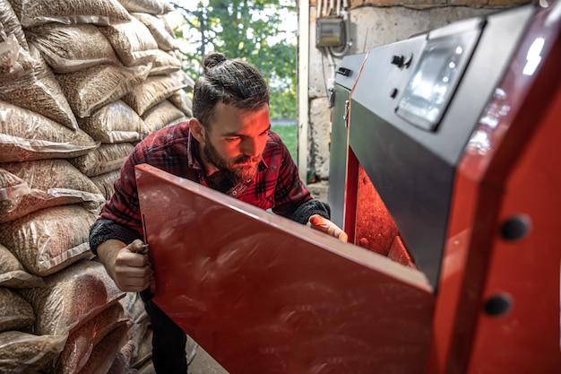 Der junge mann, der einen festbrennstoffkessel untersucht, mit biokraftstoffen arbeitet, sparsam heizt.