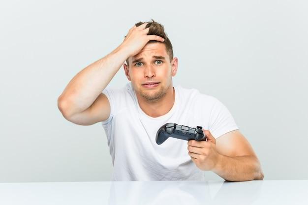Der junge mann, der einen gamecontroller hält, der entsetzt ist, hat sich an wichtiges treffen erinnert.