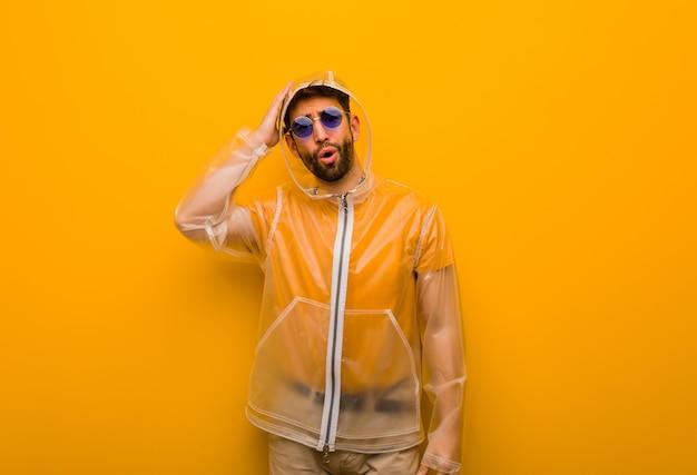 Der junge mann, der einen regenmantel trägt, war besorgt und überwältigt