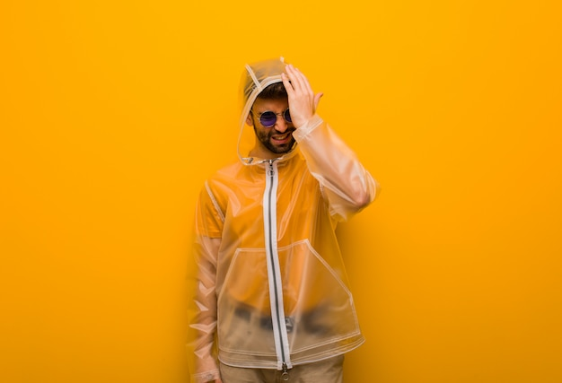 Der junge mann, der einen vergesslichen regenmantel trägt, verwirklichen etwas