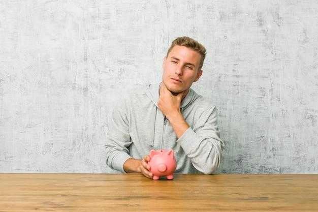 Der junge mann, der geld mit einem sparschwein spart, leidet die schmerz in der kehle wegen eines virus oder einer infektion.