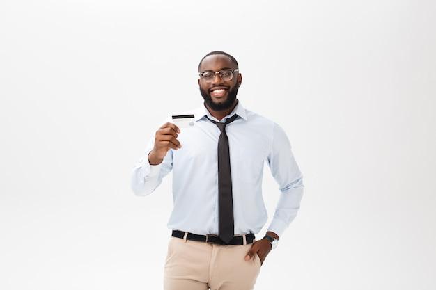 Der junge mann, der im hemd steht, zeigt kreditkarte, betrachtet das lächeln der kamera.