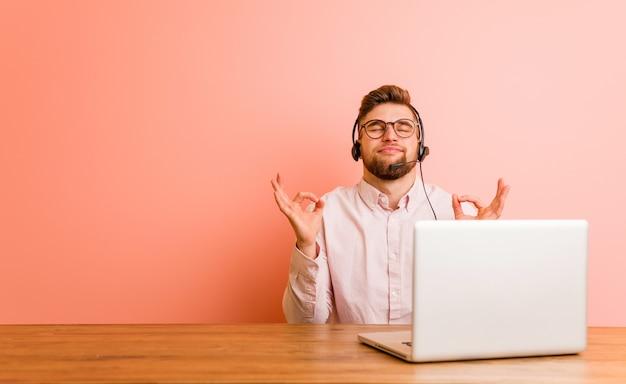 Der junge mann, der in einem callcenter arbeitet, entspannt sich nach einem harten arbeitstag und führt yoga durch.