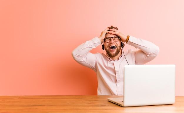 Der junge mann, der in einem callcenter arbeitet, lacht freudig und hält die hände auf dem kopf. glückskonzept.