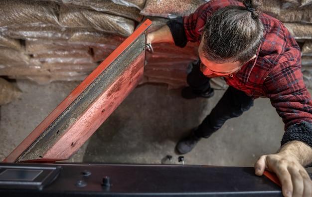 Der junge mann, der in einen festbrennstoffkessel schaut, mit biokraftstoffen arbeitet, sparsam heizt, draufsicht.