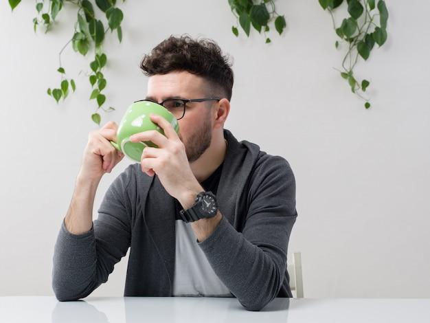 Der junge mann, der in einer brille sitzt, sieht zu, wie die graue jacke seinen saft aus der grünen tasse zusammen mit der pflanze auf weiß trinkt