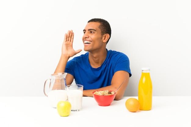 Der junge mann, der in einer tabelle schreit mit dem breiten mund frühstückt, öffnen sich